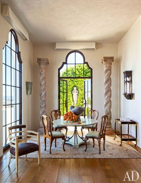 Circa-1400 Solomonic columns frame French doors in the dining area while rococo chairs surround the vintage Arturo Pani table | archdigest.com
