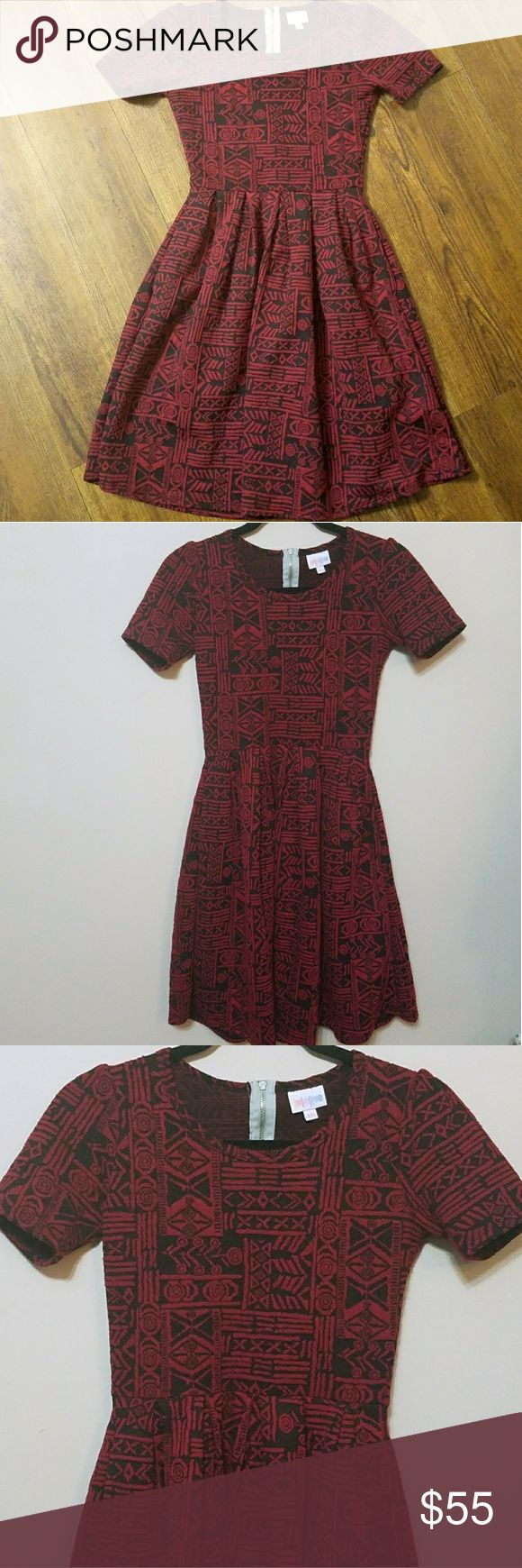 Lularoe XXS red black aztec Jacquard Amelia dress With its red and black aztec/tribal inspired print, This Jacquard Amelia dress from lularoe is super cute!  Lularoe Amelia style Red and black print Jacquard style Short sleeves Knee length Pockets on the skirt Zip back Polyester/spandex blend  The lularoe Amelia dress is stretchy and comfortable. An XXS is perfect for sizes 00 and 0!  The dress is in EXCELLENT condition - it could be mistaken for brand new!  Freshly steamed LuLaRoe Dresses