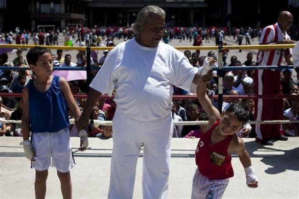 Erick Villanueva (R), 9, who was left homeless after the December 2010 torrential rains, celebrates after winning a fight in a Olympics-style street boxing championships in Caracas February 19, 2011.  REUTERS/Carlos Garcia Rawlins