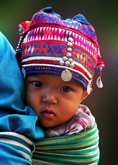 A child from the Akha tribe, one of six indigenous hill tribes  that live in the Mekong Highlands, that includes the Golden Triangle, it was given this name by Western media reporting on gun battles between large rebel drug armies in the 50's. The Akha people live in Thailand, Myanmar (Burma) Laos, Vietnam and China.
