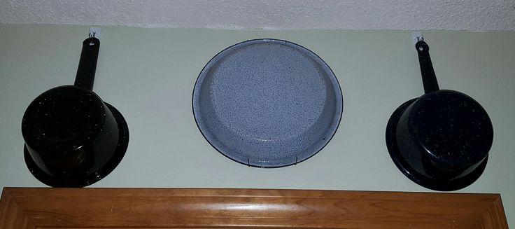 Black saucepans & gray pie pan hanging above our pantry door.