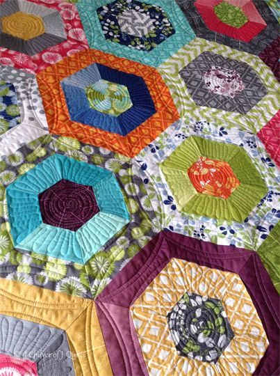 """Hexagon quilt, close up of quilting at J- Quilts (UK): """"I freehand quilted simple swirls in the centers, and some simple freehand back-and-forth in the middle section of each hexagon.  The most time-consuming part was the ruler work creating the circular movement around the hexagons, and of course the pebbling which is always time consuming yet worth it."""""""