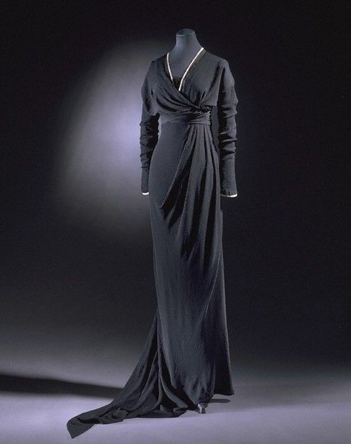 Black silk crepe half-mourning dress, 1910-2, London Black silk crepe, edged with bands of black and cream silk, the neck fitted with machine-made black lace, Worn by Miss Heather Firbank