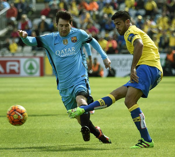 Barcelona's Argentinian forward Lionel Messi (L) vies with Las Palmas' defender Aythami Artiles during the Spanish league football match UD Las Palmas vs FC Barcelona at the Gran Canaria stadium in Las Palmas de Gran Canaria on February 20, 2016.