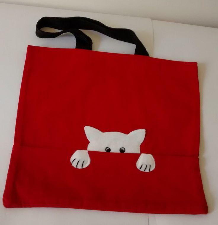 Sacola em tecido brim vermelho com aplicação gatinho em feltro branco, em ambos os lados da sacola. Alças de nylon com 23cm de altura.