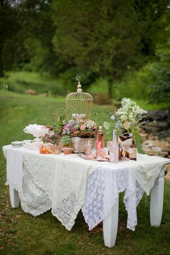 Drape tables in layers of table cloths, lace and top with flowers in little jars & tea cups.
