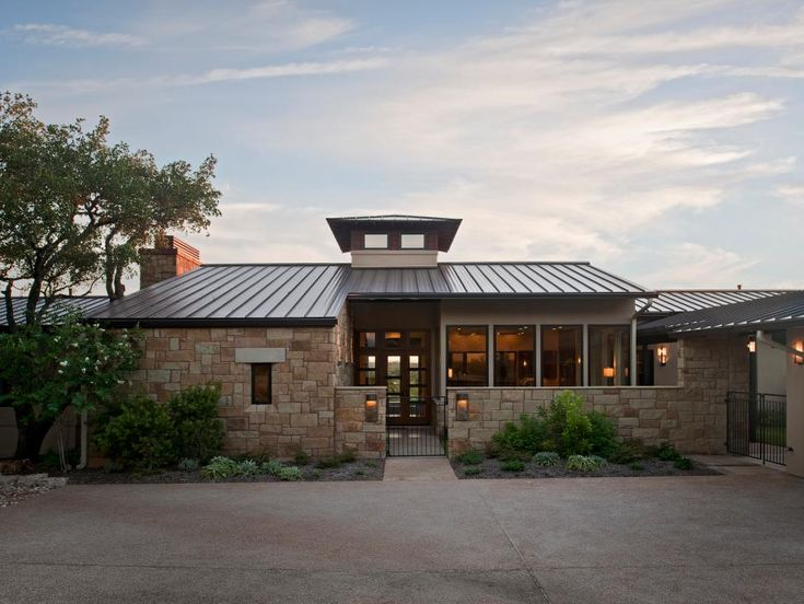 A tin roof and stacked stone are among the custom elements that make this modern home in Texas' hill country stand out. A cupola offers views of the surrounding countryside.