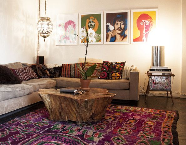 Eclectic bohemian living space. Moroccan rug & lantern, tree-stump coffee table, framed pop art, mixed global print cushions. Perfect.