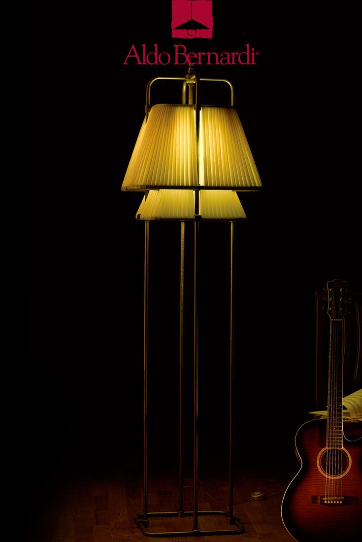 Maupiti Floor Lamp by Aldo Bernardi: four stems antique brass mobile lighting fixture on square base with single light and fabric shade fully integrated into structure. Hand-finished product.