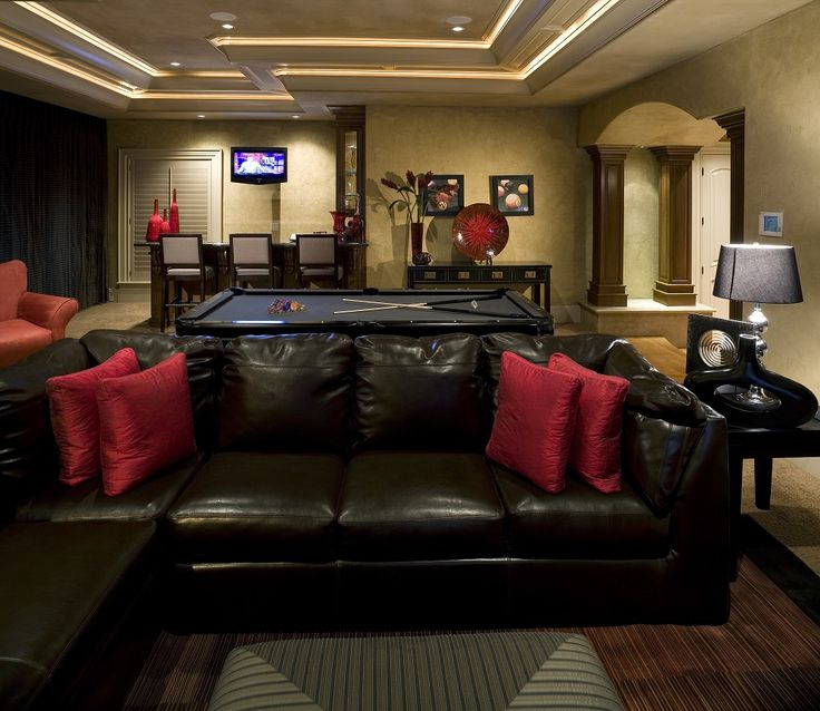 Black pool table paired with wall washer lights, black leather sectional sofa, red throw pillows and black side tables in a dark yet elegant man cave design.