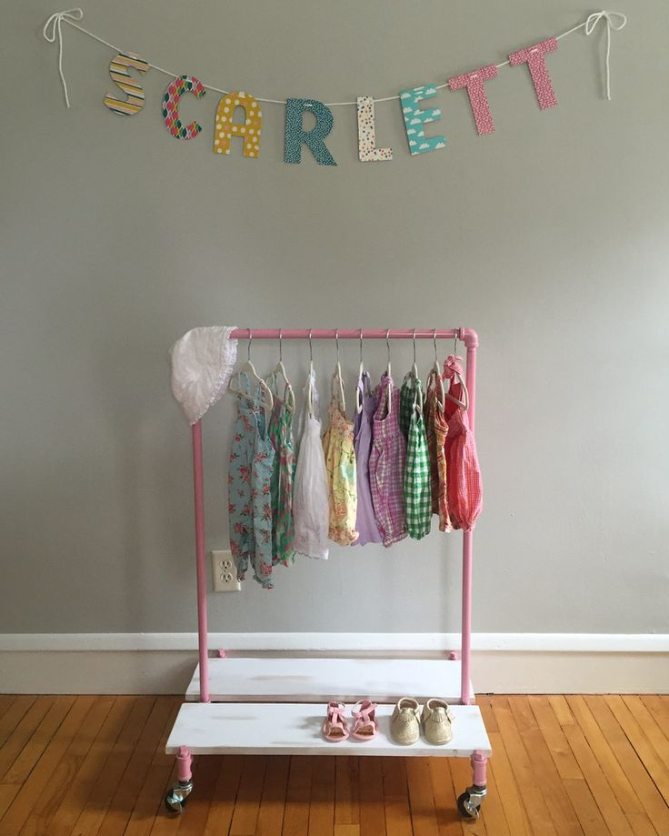 Children's clothing rack.  Easy to assemble by hand with no tools.  White wash wood platforms are removable