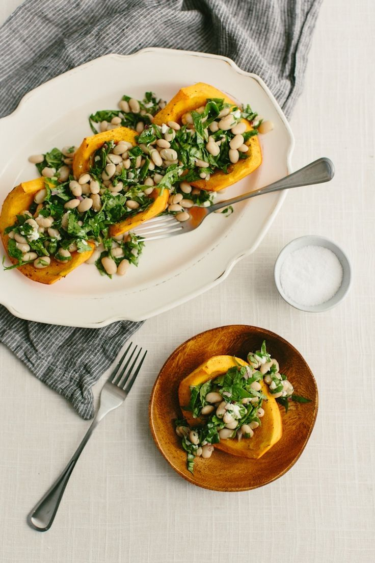 A hearty fork and knife vegetarian meal or holiday side, red kuri squash is roasted and then topped with a light white bean and spinach salad.