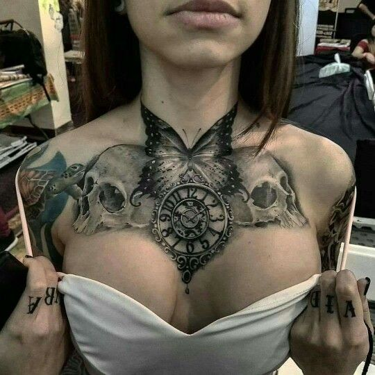 Skulls, clock, butterfly tattoo. And implants.