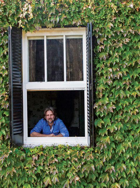 Entrada de la casa del productor de muebles Pablo Ledesma con ventanas guillotina pintadas de blanco, postigos negros y enredadera cubriendo la fachada.