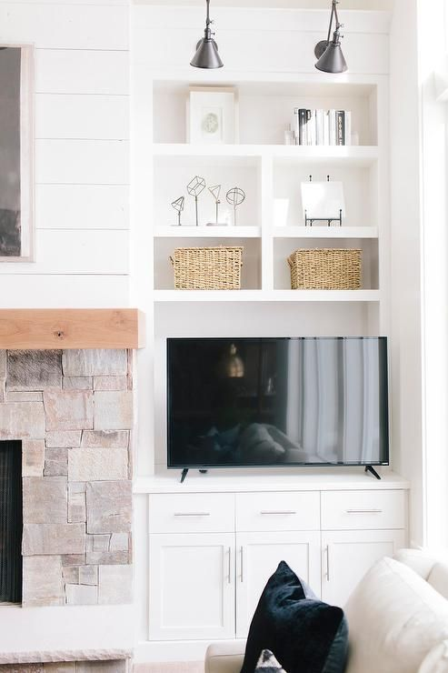 BM Simply White  Chic cottage living room features a stone fireplace accented with a wood mantle under art next to built in shelves and cabinets lined with a flat panel tv illuminated by Schoolhouse Electric Princeton Sconces.