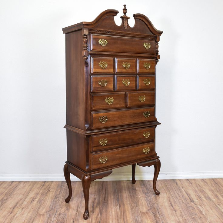 This chippendale highboy dresser is featured in a solid wood with a glossy walnut finish. This tall dresser has an intricate carved broken pediment top, curved cabriole legs and 7 long drawers. Regal storage piece perfect for additional closet space! #americantraditional #dressers #talldresser #sandiegovintage #vintagefurniture