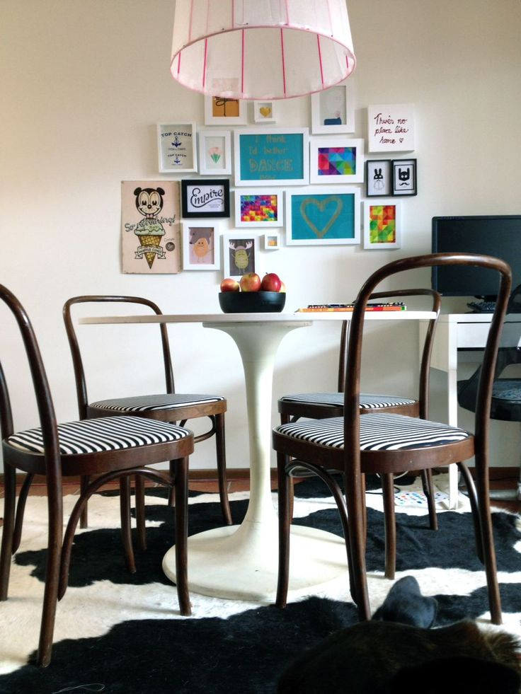 Our meals area features bentwood chairs, upholstered in b&w stripe. Fun Gallery wall, Cow hide rug, Ikea table. And salvaged pendant light shade - spray painted neon pink and covered in sheer white fabric.