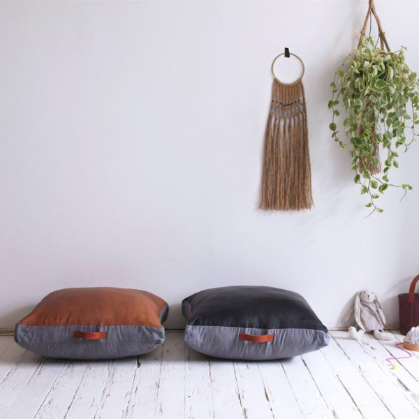 Beautiful butter soft leather floor pad with cognac leather embossed handles. Perfect for lounging around and great for kids! Grey linen backing.