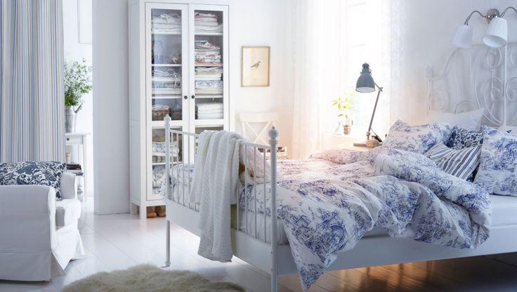 Bettwäsche!! Ein Schlafzimmer mit weißem LEIRVIK Bettgestell mit 3-teiligem EMMIE LAND Bettwäsche-Set weiß/blau, EMMIE KVIST Kissen weiß/blau und BIRGIT STRÅ Decke weiß, Gardinen aus EMMIE RAND Meterware blau, LUDDE Schaffell in Weiß und viel Bettwäsche in HEMNES Vitrinenschrank in Weiß