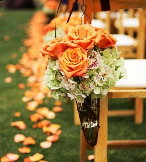 des bouquets de fleurs accrochés sur les chaises