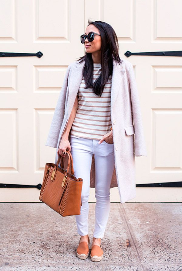 Street style look com camiseta branca listrada, calça jeans e maxi casaco.