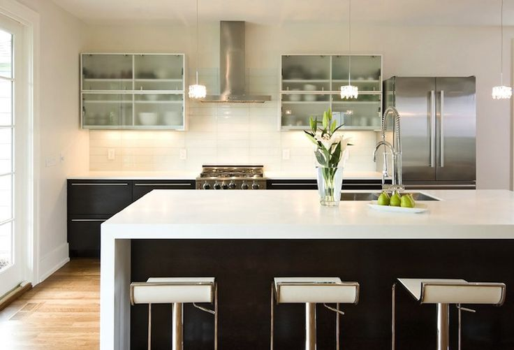 Modern kitchen with glass front upper cabinets and ...