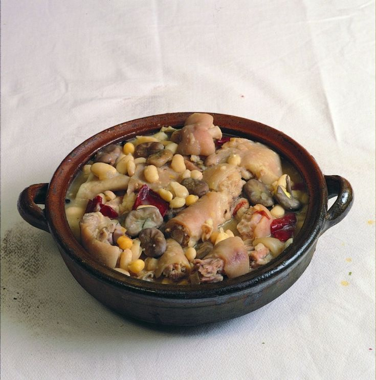 Poner las habas y las judías en remojo la víspera. En el momento de cocinar, pelar la cebolla y partirla en dos, lavar el hueso de espinazo y el de jamón, y poner todos los ingredientes, excepto morcilla, arroz y patatas, en una olla (a ser posible de barro) al fuego, cubiertos de agua. Dejar…