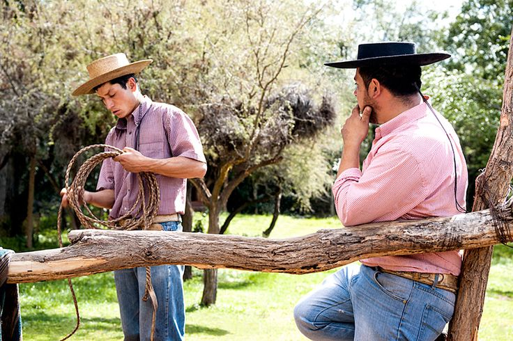 Horse farm in El Toyo region of Cajon del Maipo, Chile, South America, Arriero Victor winds up his own handmade leather lasso while his friend Osvaldo from Pique admires his craftsmanship. Waiting at teh parcela for the trip to start. Photo by Kim Walker. http://www.uniquetravelphoto.com/?p=2221