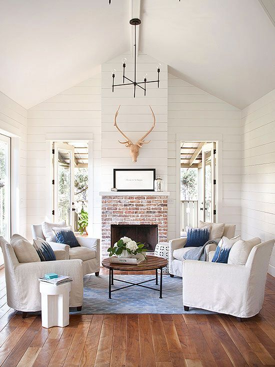 Shiplap walls || arrangement of four chairs around circular coffee table