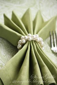 Green linen napkin is gussied up with a pearl napkin ring.