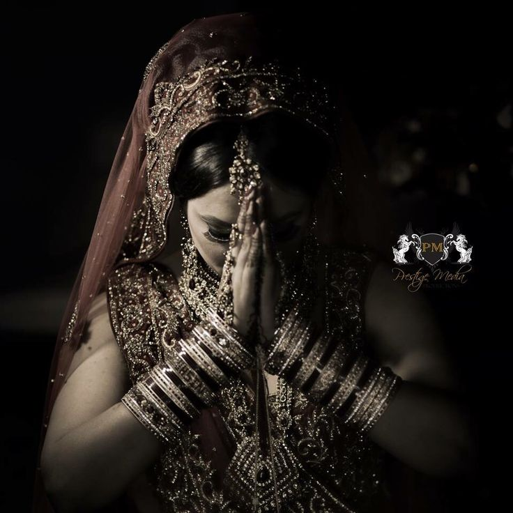 Indian bride praying before leaving home on the morning of her traditional Sikh wedding