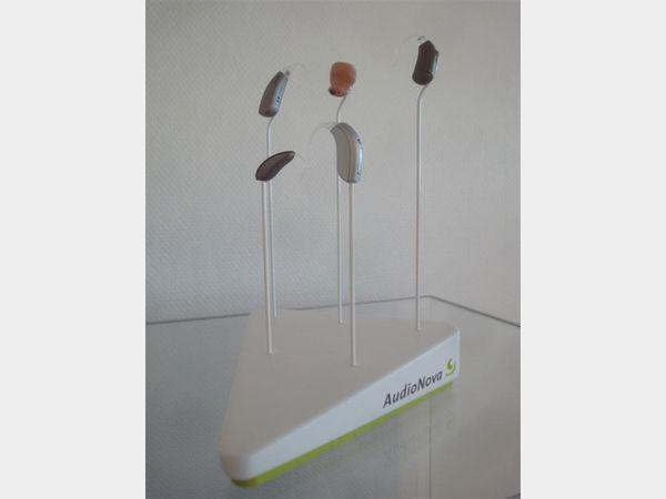 Presentatie van hoorapparaten van Audio Nova. Mdf blokje gelakt wit en groen met metalen staafjes waarop de apparaten verlijmd worden.