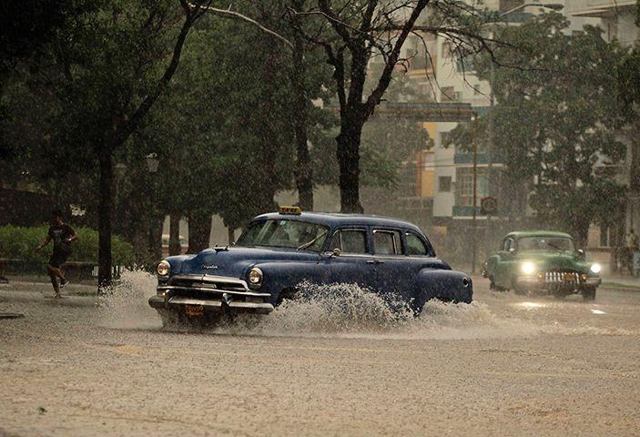 Havana, Cuba: Taxis drive through a tropical thunderstorm Photograph: Desmond Boylan/Reuters