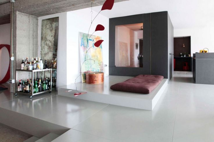 Loft: Spacious Pallars Loft Interior with Minimalist Style in Barcelona, Spain by KAYSERSTUDIO, Pallars Loft Living Area with Hanging Decorations and Maroon Futon and Art Painting Decor in Leveled Floor Area by KAYSERSTUDIO