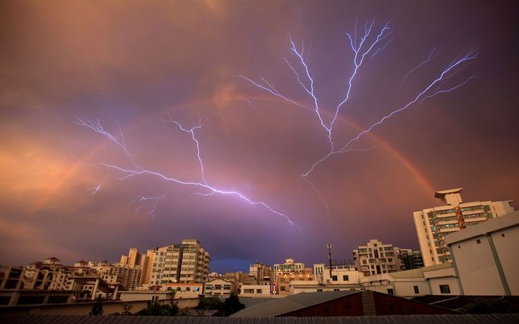 A rainbow is seen in the sky as lightning strikes after a rainstorm in Haikou, Hainan province, China: China Daily, Rainbows, Favorite Photographs, Mother Nature Earth, Lightning Rainbow, Lightning Photos, Photography Stuff