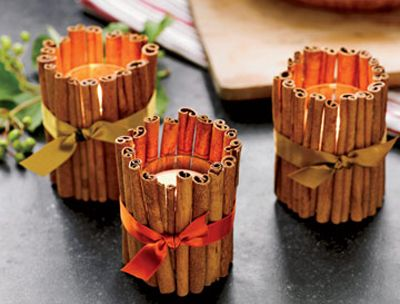 Hot glue cinnamon sticks around a candle votive and add a ribbon detail. Cozy glow and a great smell too!:
