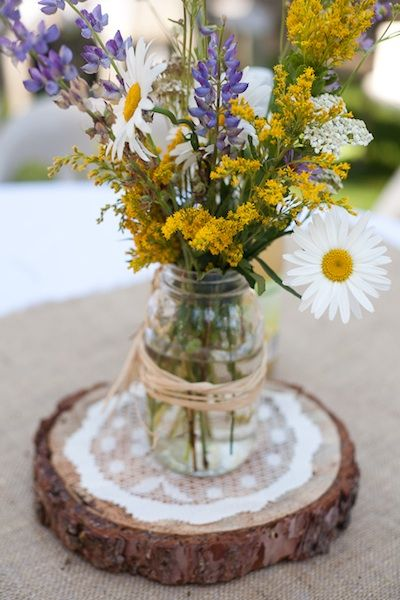 Wedding Flowers: Wildflowers as centerpieces on pieces of wood that are cut by Chad (good way to get him involved) :)  on top of burlap... simple and sweet. I imagine the tables like this.... different vase/flower arrangement, but same base...linen, burlap, doily...reva 12/12/12