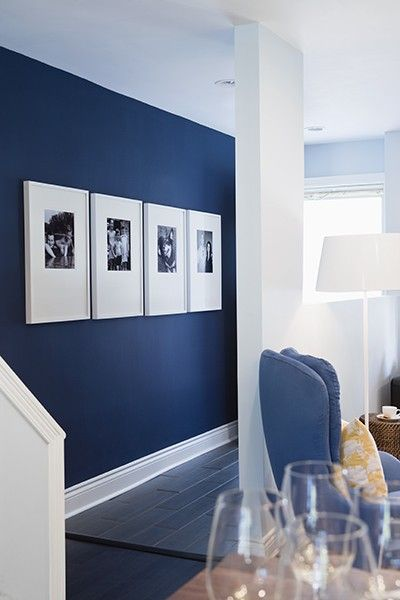 White framed bw pics on blue wall adds the white we need the navy blue wall white trim so pretty with black and whites in white frames pop of yellow