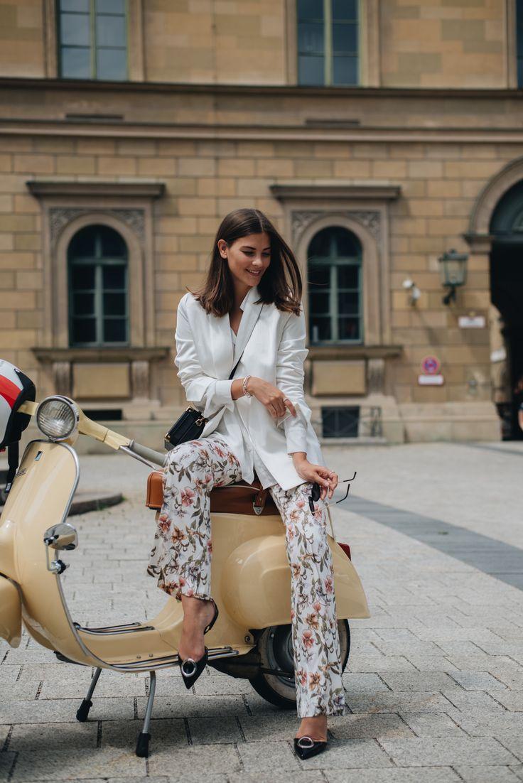 Nina Schwichtenberg trägt zu ihrer geblümten Hose eine weiße Bluse & weißen Blazer, dazu eine Koffertasche und Pandora Schmuck. Mehr auf www.fashiioncarpet.com