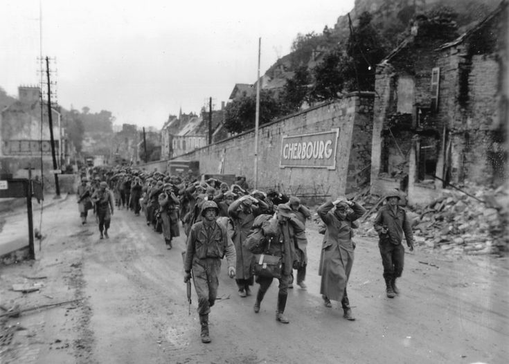 Captain W.H. Hooper, Company Commander, L Company, 314th IR, 79th ID leads a column of German POW's with officers at its head guarded by his men up the Cherbourg - Paris Road. They are heading south towards POW cages created in the Montagne du Roule area. Captain Hooper was dead within a few days of this picture being taken, KIA in the La Haye-du-Puits area in early July.