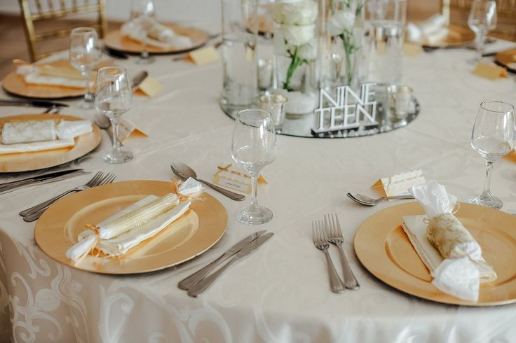 Monte Vista Venue white and gold table setup with a white tablecloth, gold under plates, gold and lace name cards, gold tiffany chairs and a all white and glass centerpiece