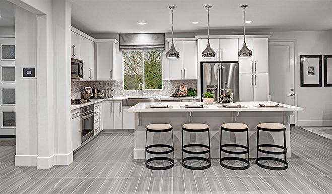 White cabinets and countertops and stainless-steel appliances give this Irvine, CA, kitchen a modern look and feel | Nolan plan by Richmond American