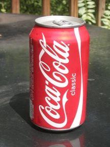 Photo shows a pop-top aluminum can of Coca-Cola.