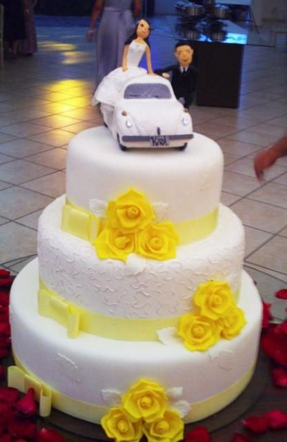 white with yellow   Three tier white round wedding cake with yellow roses and bride and ...