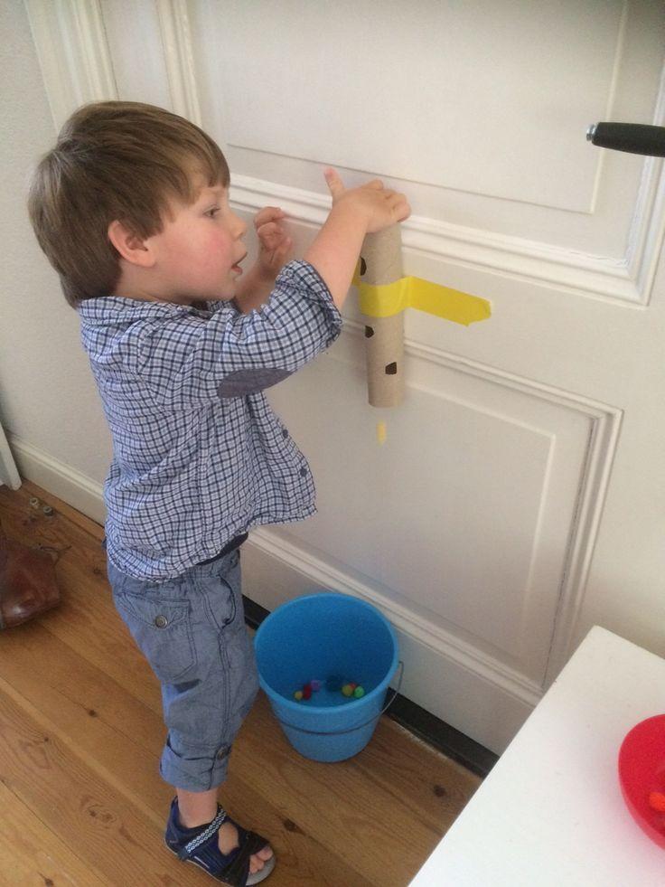 DIY speelgoed voor een peuter van 2 jaar maken. Leuk spel met een keukenrol en pompoms, zeker een half uur vertier!