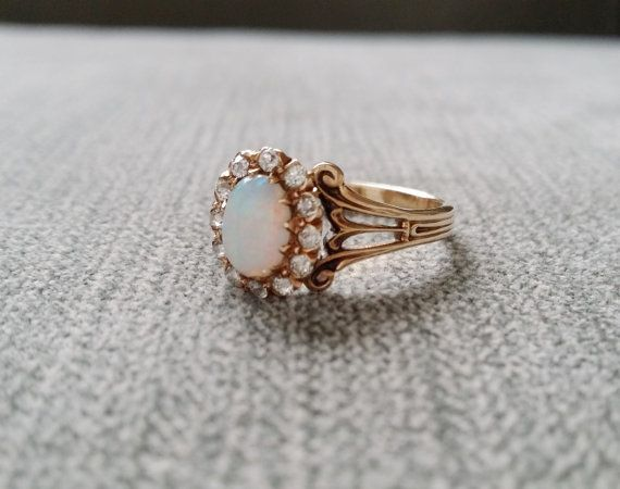 This Stunning Antique Ring features a 14K Antique Gold Setting with .90 carat Natural Opal and 12 Natural Diamonds measuring .24 carats. Makes a