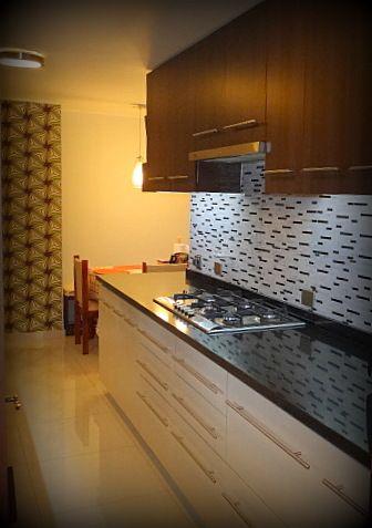 Cocina empotrada, mueble enchapado, tiradores metálicos satinados, cubierta de granito, salpicadero en mosaico de mármol, luces LED.