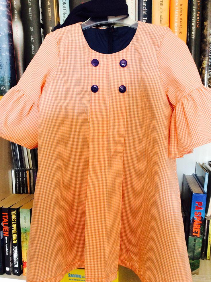 Orange-rutig bomull, blått foder, blixtlås och knappar. Till K juni 2016 med blått hårband med blomma.