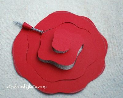 "Rolled Paper Flower Tutorial Cut a circle out of paper. I used cardstock. (My circle was about 3 1/2"" across, and it made a rose about 1 1/2"" across.) Cut out the circle, making a wavy edge as you go.Now take your scissors and start cutting a spiral wavy line from the outside of the circle to the middle. When you are finished, cut off the point at the beginning. Keep wrapping the paper around in a circle. I like to wrap it tight and then let it uncurl later."