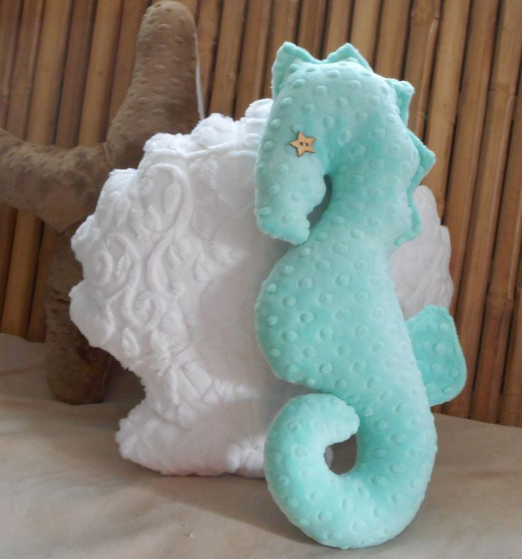 Seahorse plushie pillow stands 17 inches tall and is made from a opal colored minky dot fabric. Features outline stitching around the spikes to head and neck. A hand stained wooden button represents this regal seahorses eye. Pictured with a white minky vine embossed fabric scallop shell pillow and a cocoa colored minky dot starfish pillow also in my shop. Perfect accent piece to any nautical decor or nautical baby nursery